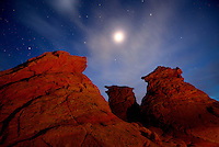 The full moon and a starry sky above sandstone mounds, Vermilion Cliffs National Monument, USA.