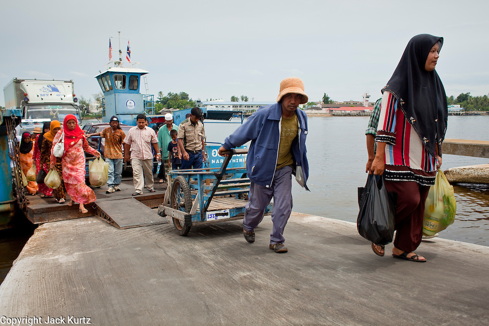 Sept. 27, 2009 -- TAK BAI, THAILAND: People arrive in Tak Bai, Narathiwat, Thailand on a ferry from Malaysia.  The Thai-Malaysia border in Narathiwat province sees a steady stream of cross border trade but tourism from Malaysia which once flourished for Malaysians who wanted to drink and enjoy other vices prohibited in Muslim Malaysia has all but stopped since violence by Muslim insurgents in south Thailand destroyed several tourist hotels. Photo by Jack Kurtz / ZUMA Press