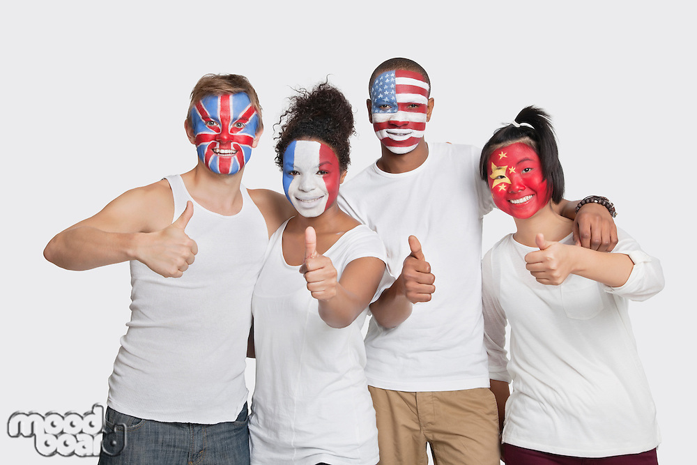 Portrait of happy Multi-ethnic group of friends with various national flags painted on their faces gesturing thumbs up against white background