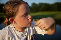 YOUNG FEMALE ANGLER PRETENDING SHE'S ABOUT TO KISS A BLUEGILL