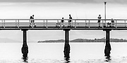Fishermen and pedestrians on a section of Orakei Whalf, Okahu Bay, Auckland, New Zealand.