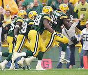 GREEN BAY, WI - SEPTEMBER 25:  Defensive end Kabeer Gbaja-Biamila #94 of the Green Bay Packers heads for the end zone with a trio of blockers after recovering a fumble that was reversed after a challenge in the game against the Tampa Bay Buccaneers at Lambeau Field on September 25, 2005 in Green Bay, Wisconsin. The Buccaneers defeated the Packers 17-16. ©Paul Anthony Spinelli *** Local Caption *** Kabeer Gbaja-Biamila