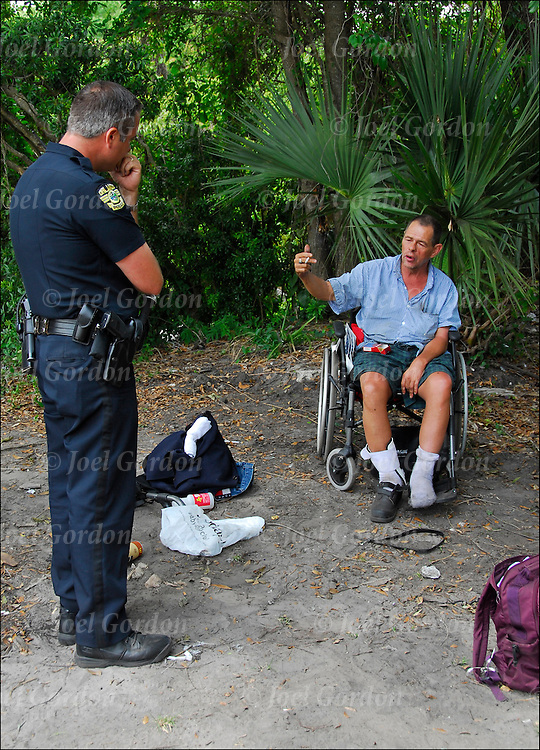 Police officer questioning homeless man in wheelchair about homeless woman who over dossed on drugs early that day at the Macon-Delta a camp . Homeless people living in the woods of Orlando. They are called the tree people by other homeless street people.