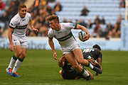 London Irish wing Ollie Hassell-Collins (11) looks to pass in the tackle during the Gallagher Premiership Rugby match between Wasps and London Irish at the Ricoh Arena, Coventry, England on 20 October 2019.