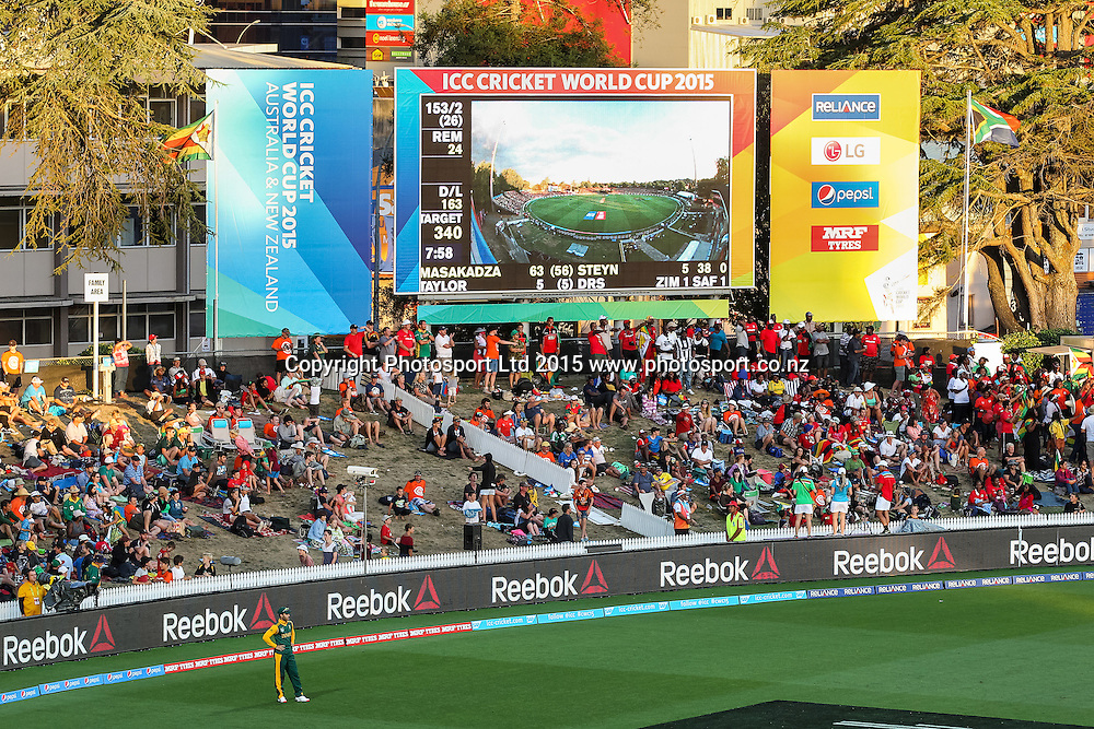 Cricket fans sit under the big screen during the ICC Cricket World Cup match - South Africa v Zimbabwe at Seddon Park, Hamilton, New Zealand on Sunday 15 February 2015.  Photo:  Bruce Lim / www.photosport.co.nz