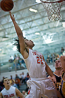 JEROME A. POLLOS/Press..Post Falls High's Marcus Colbert extends and elevates toward the hoop over the Lewiston defense during the second half of the 5A Region 1 tournament Friday. The No. 1 seeded Trojans beat the No. 4 Bengals 76-50.