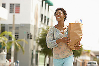 Smiling young woman carrying groceries portrait