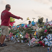 TUESDAY, FEBRUARY 27- 2018---PARKLAND, FLORIDA--<br /> Coral Springs resident Craig Lusthaus tosses flowers on a makeshift memorial built by mourners  at Marjory Stoneman Douglas High School  for the victims of February 14 school massacre.<br /> (Photo by Angel Valentin/FREELANCE)