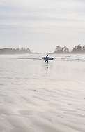 A surfer at Chesterman Beach during low-tide, in Tofino, British Columbia, Canada