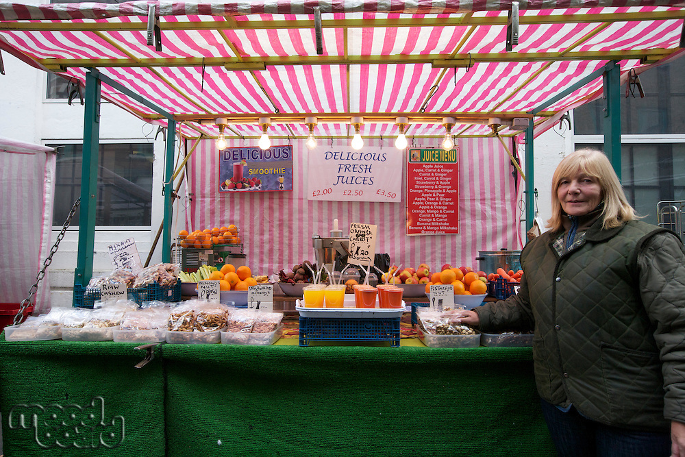 Portrait of a happy senior fruit stall owner standing in market