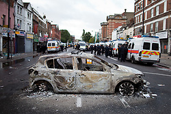 © Licensed to London News Pictures . FILE PICTURE DATED 07/08/2011 . Tottenham , UK . The burned out shell of a police car , melted in to the tarmac in the centre of Tottenham High Road . Vehicles and buildings were set alight during a night of rioting in Tottenham . Photo credit : Joel Goodman/LNP