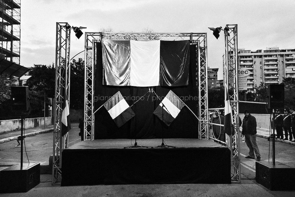 "A stage with three Italian flags is set up minutes before Gianfranco Fini, former President of the lower house of the Italian parliament and leader of the ""Future and Freedom"" party in outgoing Prime Minister Mario Monti's coalition, delivers a poorly attended speech, in Palermo on January 17th 2013.<br /> <br /> The stage was temporarily built in via d'Amelio, where anti-mafia magistrate Paolo Borsellino was assassinated by a car bomb placed by the mafia in 1992. Magistrates Paolo Borsellino and Giovanni Falcone were investigating on the relationships between the Mafia and politics in the months preceding their death that same yeaer. <br /> <br /> ###<br /> <br /> Palermo, febbraio 2013. Un palco allestito per l'arrivo di Gianfranco Fini, Presidente della Camera dei Deputati uscente e leader del partito Futuro e Libertà nella coalizione del premier Mario Monti, durante un omaggio in via d'Amelio al giudice Paolo Borsellino, ucciso dalla mafia nel 1992."