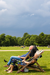 London, June 2nd 2017.  A couple relax on deck chairs, soaking in the sun in Hyde Park as clouds build up in the background ahead of forecast thunderstorms.