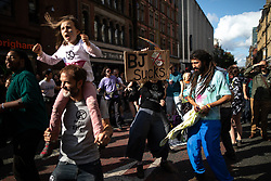 © Licensed to London News Pictures. 31/08/2019. Manchester, UK. People dance to music in front of a stage on Deansgate . Extinction Rebellion block roads around Deansgate in Manchester City Centre , during days of planned disruption organised by environmental campaigners . Manchester City Council has declared a climate emergency but activists say the council's development plans do not reflect this . Photo credit: Joel Goodman/LNP