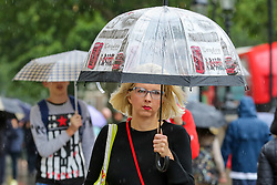 © Licensed to London News Pictures. 18/06/2019. London, UK. A woman shelters from the rain in Westminster under a London branded umbrella. The Met Office has issued a yellow weather warning for London as torrential rain, hail and lightning is forecasted. Photo credit: Dinendra Haria/LNP