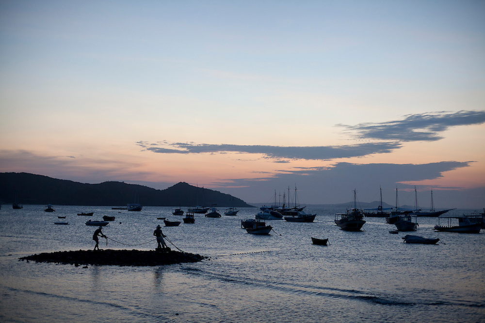 Dusk at Buzios Bay, with a view of the Fishermen In The Water sculpture by Christina Motta