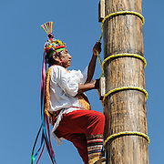 A man climbs to the top of a tall pole as part of recreating a traditional Mayan ceremony of swinging from a tall pole suspended only by ropes at Xcarat Maya theme park south of Cancun and Playa del Carmen on Mexico's Yucatana Peninsula.