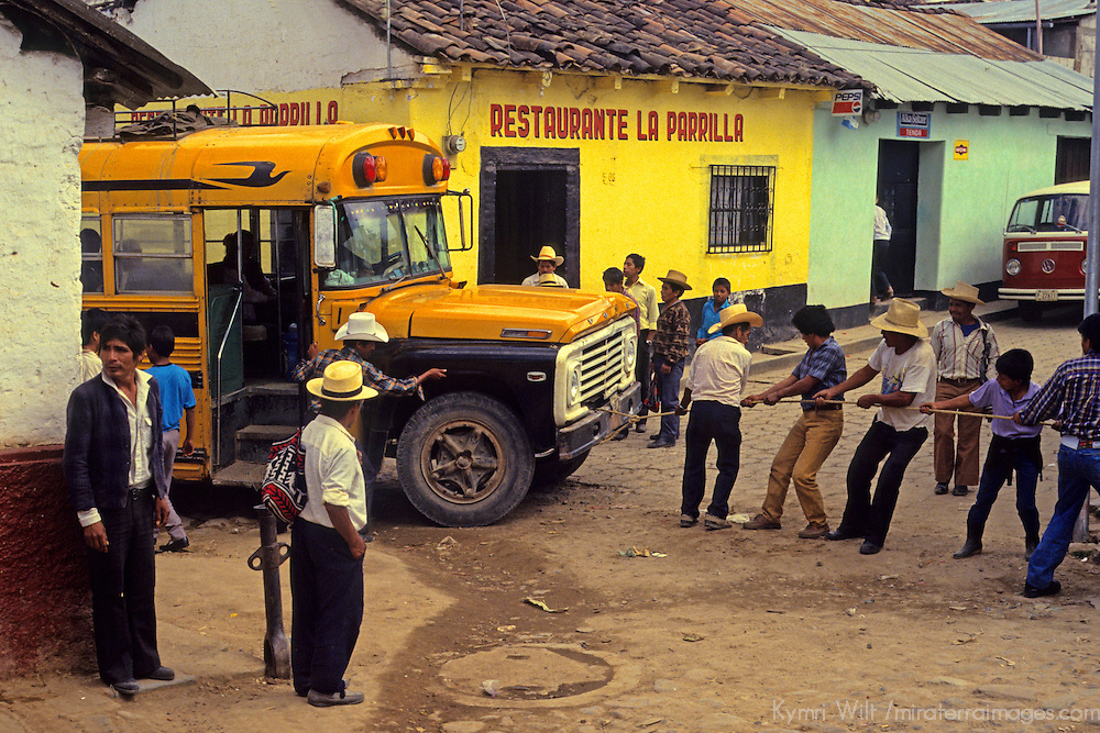 Central America, Latin America, Guatemala, Chichicastenango. Locals help tow a broken down bus out of the intersection.