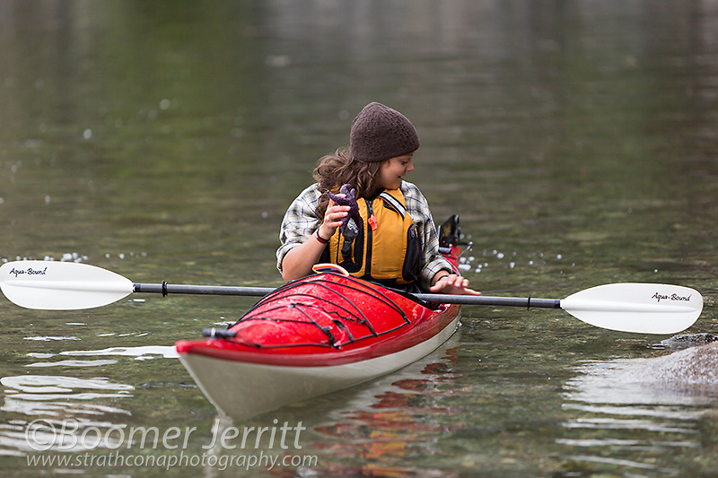 A young Kayaker explores inter tidal life in waters near Quadra Island.  Discovery Islands, British Columbia, Canada
