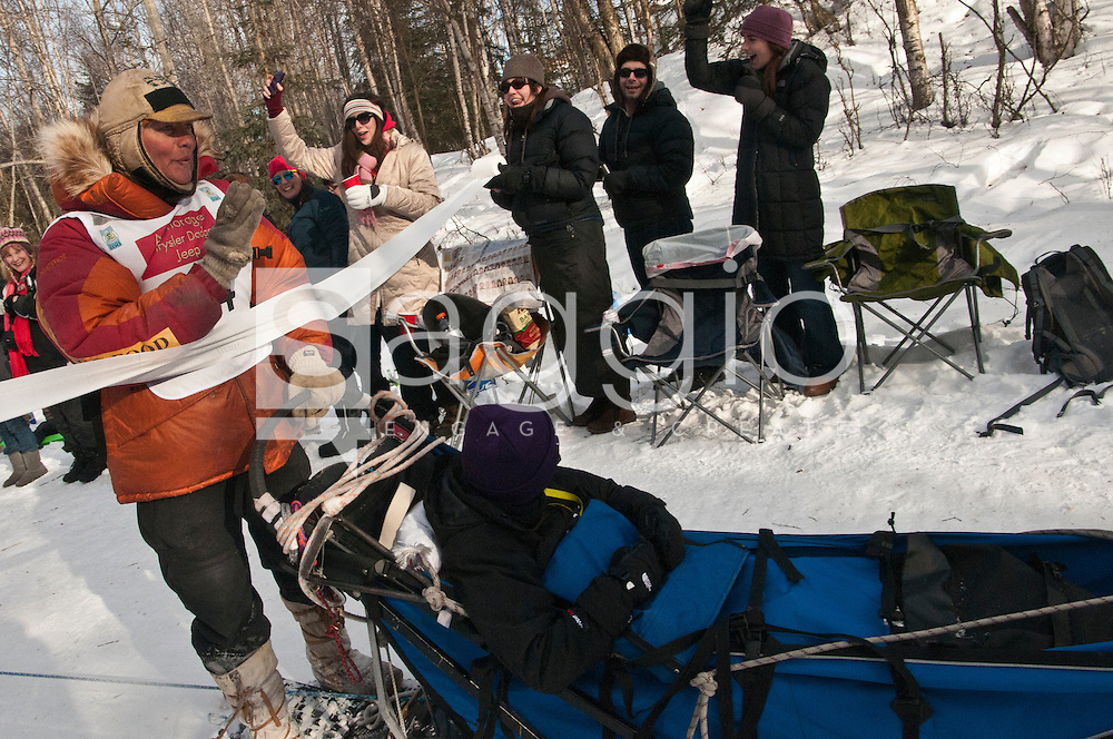 Sleddog fans shout and wave as musher Billy Snodgrass and Iditarider Courtney Cronin ride along the Chester Creek Trail during the 2011 Iditarod Ceremonial Start.