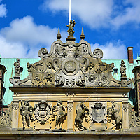 Portal Relief on Terrace Wing at Frederiksborg Castle in Hiller&oslash;d, Denmark <br /> This splendid relief forms the top of the Terrace Wing portal which leads from the courtyard and the Neptune Fountain towards the Royal Wing of the Frederiksborg Castle.  In the center is the monogram C4 which stands for Christian IV, the King of Denmark and Norway. On the left is his statue and opposite it is Anne Catherine of Brandenburg who was his queen from 1597 until 1612.  Also notice the two unicorns around the coat of arms.  Their significance is that, according to legend, the Throne Chair of Denmark is constructed from the horn of unicorns.