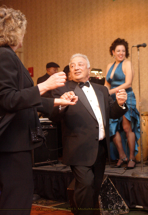 Lee (left) and Tony Massoud dance to the music of Gina Stough (right) and Son del Caribe at the 17th Artemis Center Gala, Saturday night.