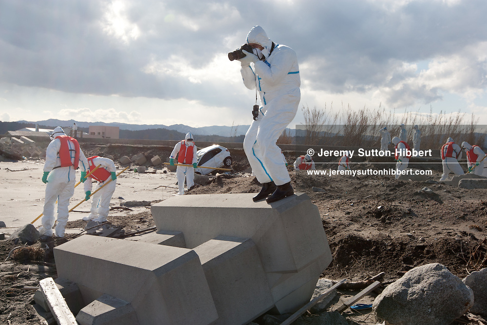 Within sight of the crippled Fukushima Daiichi nuclear plant, American war photographer James Nachtwey photographs Japanese police searching on Ukedo beach for bodies of tsunami victims, within the evacuated, and now uninhabited 20km exclusion zone around Fukushima Daiichi nuclear plant, in Namie, Japan, on Monday 27th February 2012..The exclusion zone used to be home to approximately 73,000 people, but all have been evacuated by the government and are now restricted from returning home due to high levels of radiation contamination from the explosions at the TEPCO owned Fukushima Daiichi nuclear plant, following the earthquake and tsunami of  March 11th 2011..Due to the towns and zone being uninhabited the police patrol to prevent crime and theft from unoccupied properties and businesses.