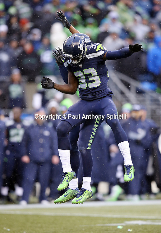 Seattle Seahawks defensive back Kelcie McCray (33) leaps and celebrates with a hip bump during the 2015 NFL week 16 regular season football game against the St. Louis Rams on Sunday, Dec. 27, 2015 in Seattle. The Rams won the game 23-17. (©Paul Anthony Spinelli)
