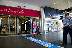 © Licensed to London News Pictures. 13/06/2020. London, UK. A man wearing a face covering walks past a 'KEEP CLEAR' sign outside Wood Green Shopping Mall in north London as it prepares to re-open on Monday. The government has announced that all non-essential retailers can re-open on Monday 15 June as the coronavirus lockdown restrictions are eased. Photo credit: Dinendra Haria/LNP