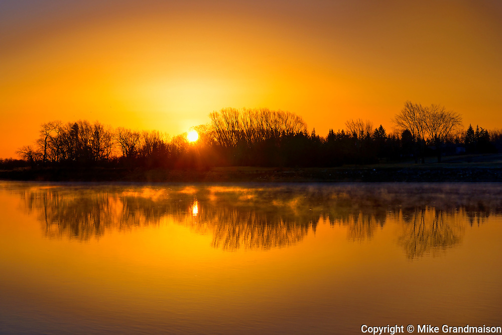 Reflection of trees in Red River at sunrise<br /> Lockport<br /> Manitoba<br /> Canada