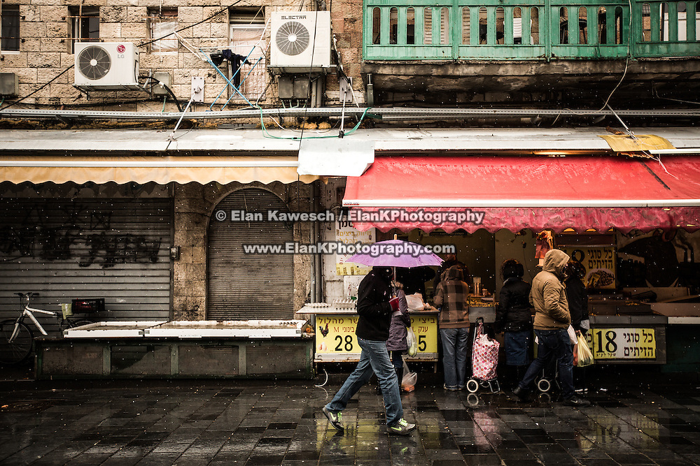 People walk down the middle of a road during a rain storm at The Mahane Yehuda Shuk on January 9, 2015 in Jerusalem, Israel. (Photo by Elan Kawesch)