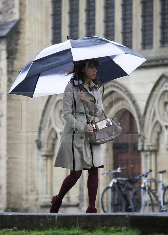 © Licensed to London News Pictures. 05/05/2015. Bristol, Avon, UK. A woman walking under her umbrella in the rain past College Green in Bristol this morning, 5th May 2015. Rain showers and strong, blustery winds have been sweeping up the South West of England, with brighter, but still windy weather expected later. Photo credit : Rob Arnold/LNP