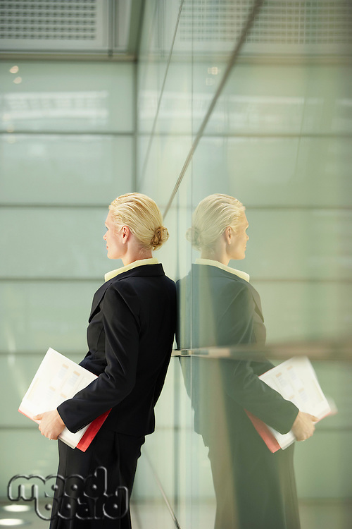 Businesswoman and Reflection in Office Corridor