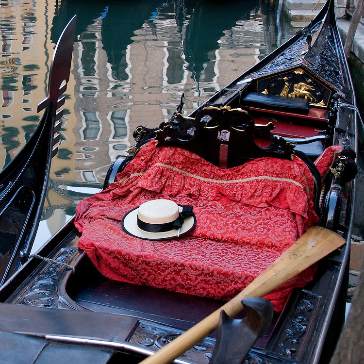 A gondolier's hat lies on an opulent cushion in s beautiful gondolier.