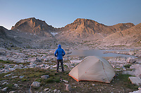 Adult male wearing blue down jacket enjoying the view at backcountry camp in Indian Basin, Fremont and Jackson Peaks are in the distance, Bridger Wilderness,  Wind River Range Wyoming