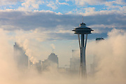 The Space Needle and several other Seattle skyscrapers are visible through thick morning fog. This scene was captured from Kerry Park in Seattle, Washington.