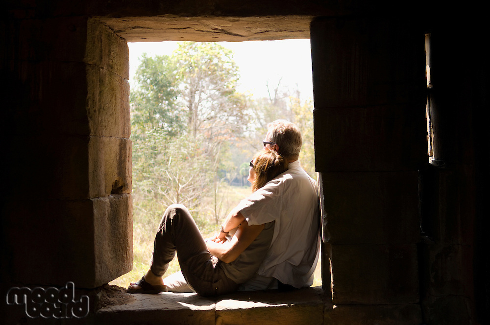 Couple Cuddling in Window of Stone Building