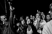 Palermo, Italy, 25 October 2012: People clap their hands during a speech of founder of the Five Stars Movement Beppe Grillo, 64, supporting candidate for Governor of Sicily Giancarlo Cacielleri, a 37 years old surveyor from Caltanisetta,  in Piazza Magione Palermo, Italy, on October 25 2012. Beppe Grillo, a comedian turned political guru, Grillo campaigned actively in Sicily, swam across the channel that separates the island from the rest of Italy, scaled its active volcano, Mount Etna, and drawed thousands of Sicilians to campaign rallies for his derisive stand-up routines.<br /> <br /> The direct elections in Sicily for the President of the Region and its representatives will take place on Sunday 28 October 2012, 6 months ahead of the end of the terms of office of the current legislature. The anticipated election of October 28 take place after Raffaele Lombardo, former governor of Sicily since 2008, resigned on July 31st. Raffaele Lombardo is under investigation since 2010 for Mafia ties. His son Toti Lombardo is currently running for a seat in the Sicilian Regional Assembly in the coalition of Gianfranco Micciché, a candidate for the Presidency of the Region. 32 candidates belonging to 8 of the 20 parties running for the Sicilian elections are either under investigation or condemned. ### Palermo, Italia, 25 ottobre 2012: il pubblico applaude il fondatore del Movimento 5 Stelle Beppe Grillo, 64 anni, durante  un comizio in Piazza Magione per sostenere il candidato alla Presidenza della Regione Sicilia Giancarlo Cancelleri, un geometra di 37 anni di Caltanisetta, a Palermo il 25 ottobre 2012.<br /> <br /> Le elezioni in Sicilia per la votazione diretta del presidente della regione e dei deputati all'Assemblea regionale (ARS) si terranno domenica 28 ottobre, in anticipo sulla scadenza naturale dell'attuale legislatura, prevista ad aprile dell'anno prossimo. In Sicilia si vota in anticipo dopo le dimissioni del 31 luglio scorso di Raffaele Lombardo, eletto presidente della regione