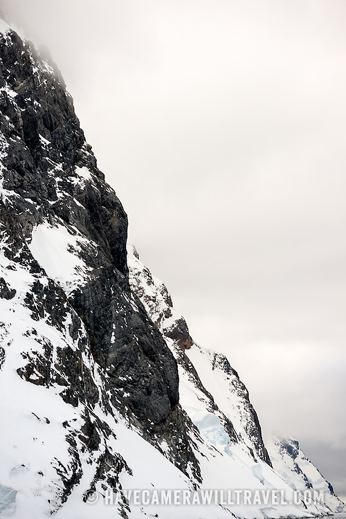 "Steep rocky cliffs reach down to the waterline of the Lemaire Channel on the western coast of the Antarctic Peninsula. The Lemaire Channel is sometimes referred to as ""Kodak Gap"" in a nod to its famously scenic views."