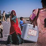 A volunteer carrying a cold storage box filled with vaccine calls the children at a stone crushing site, to come and be immunized during the 'door-to-door' activity near the city of Jodhpur, Rajasthan.