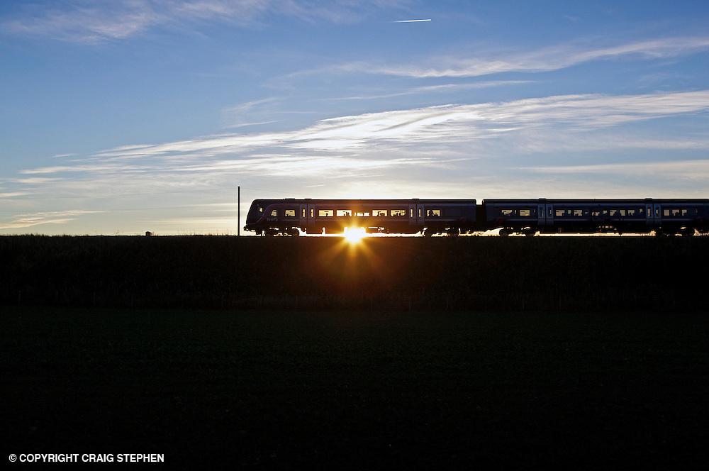A commuter train near Edinburgh at sunset