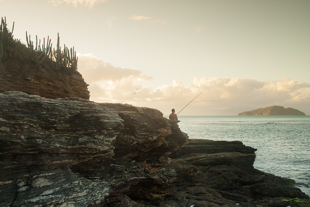 A man fishes off Tartaruga beach, B&uacute;zios, Brazil. <br /> Pescador, B&uacute;zios Brasil