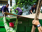 11 JULY 2017 - BANGKOK, THAILAND: Bangkok city workers put trash into a waiting truck while clearing 20 homes from the Khiao Khai Ka community along the Chao Phraya River. The community is the first to be evicted as the city goes ahead with its plan to build a 14 kilometer long (22 mile) riverfront promenade. Thousands of families are expected to be evicted to make way for the promenade. Residents in the Khiao Khai Ka community agreed to leave voluntarily and will receive compensation for their homes. The exact amount of the compensation has not been determined.      PHOTO BY JACK KURTZ