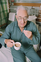 Elderly patient on medical ward taking medication with cup of tea,
