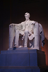 Interior of Lincoln Memorial in Washington DC facing the carved stone statue of Abraham Lincoln at night