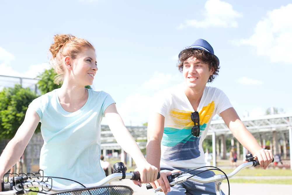 Smiling couple looking at each other while cycling in city