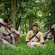 Collin Robinson, 17, center, of Oxford, Alabama, rests in the shade with other reenactors prior to participating as the 47th North Carolina in Pickett's Charge, during the Sesquicentennial Anniversary of the Battle of Gettysburg, Pennsylvania on Sunday, June 30, 2013.  A pivotal moment in the Civil War, over 50,000 soldiers died in the battle which spanned 3 days from July 1-3, 1863.  Later that year, President Abraham Lincoln returned to Gettysburg to deliver his now famous Gettysburg Address to dedicate the cemetery there for the Union soldiers who died in battle.  John Boal photography
