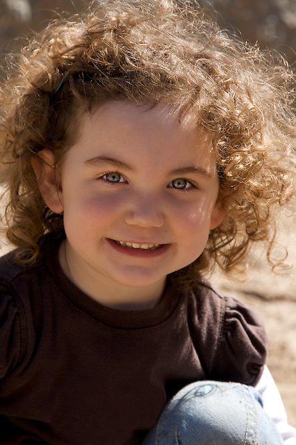 little girl with curls smiling at the camera