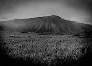 Gunung Kursi (Mt. Kursi), an extinct volcano that rises from the perfectly flat grassland that clothes the floor of the massive crater it shares with Gunung Bromo (Mt. Bromo).  Java, Indonesia.