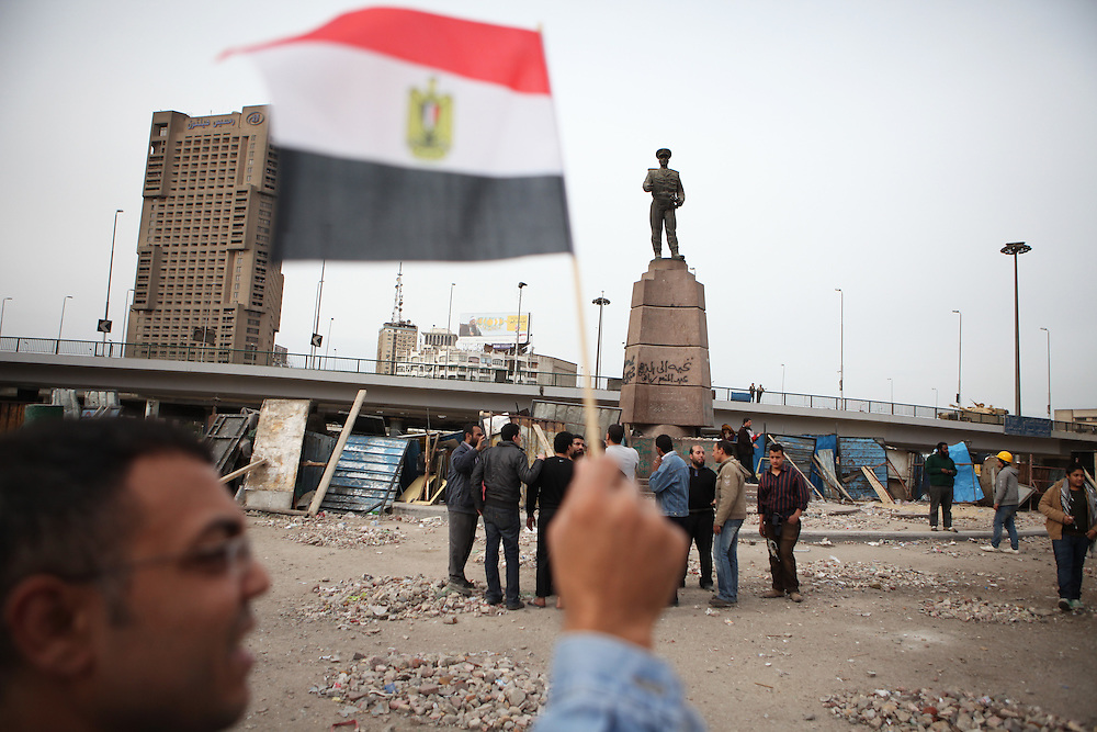 A man holds an Egyptian flag at a site near Tahrir Square where a day earlier clashes took place between protesters and Mubarak's thugs.